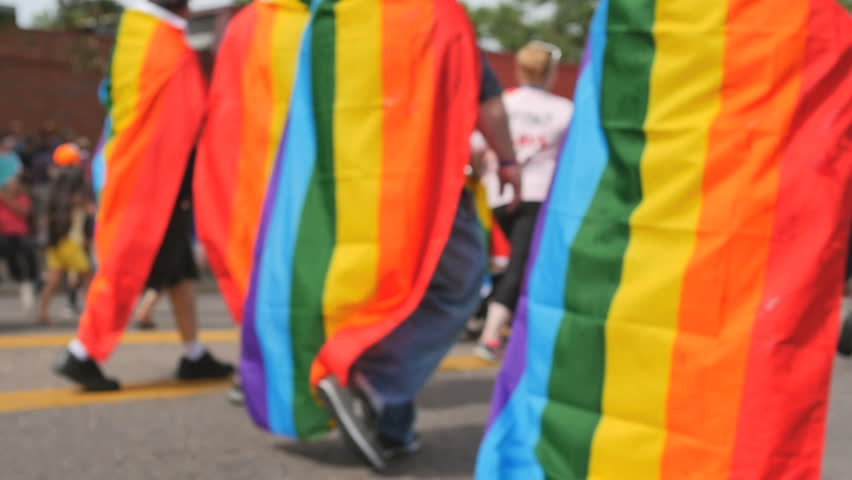 DENVER, COLORADO - CIRCA JUNE 2015. Marchers wearing rainbow flags in Gay Pride parade walk down Colfax Avenue during pride festival. slow motion. Symbol of LGBT GLBT transgender rights love equality