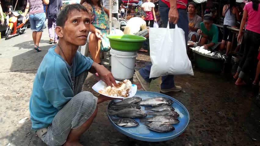 LAGUNA, PHILIPPINES - JULY 16, 2015: Tilapia fish sold at street wet market while eating lunch due to lack of market hygienic facilities