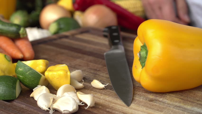 Chef cutting yellow pepper with vegetables in the background,South Africa | Shutterstock HD Video #10840994