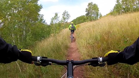 Mountain biking POV, Go Pro following another rider fast on single-track trail to view, Wasatch Crest Trail, Wasatch Mountains, Utah.