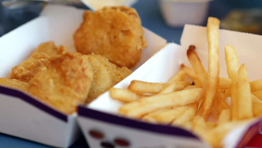 Kid eating french fries and nuggets at fast food