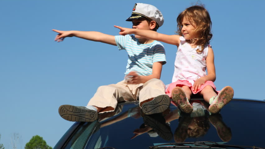 boy in captain's cap and his little sister sit on roof of car against blue sky pointing somewhere with their hands, then twist imaginary driving wheel