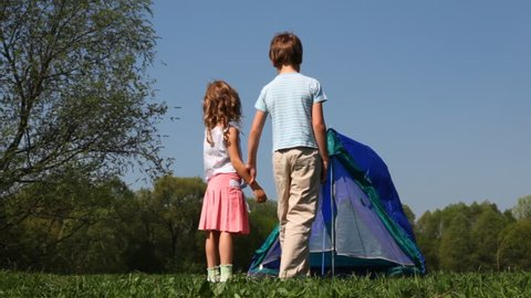 boy and little girl put up tent in woods hot summer