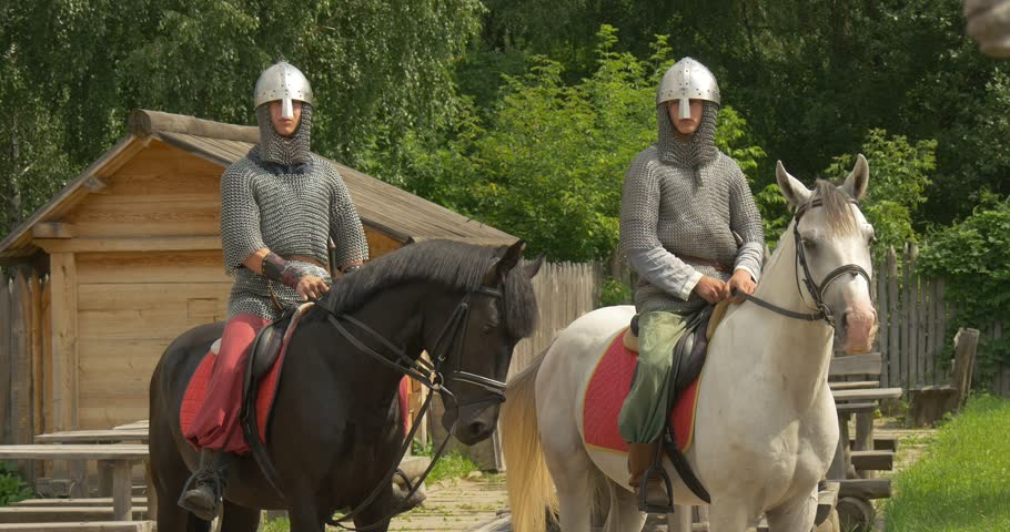KIEV/UKRAINE - AUG 17 2014: Two Actors, Horsemen, Knights, mid shot, Brown And White Horses, horsemem are in Chain Armors and Helmets, green and pink pants, horses are chewing, wooden fence,