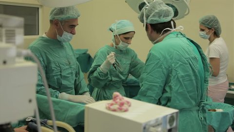 Surgical team performing surgery operation, cesarean section. Caesarean section, c-section. Gynecologists and midwifes giving birth. Maternity ward. Infant in maternity hospital. Gynecology. 30 fps.