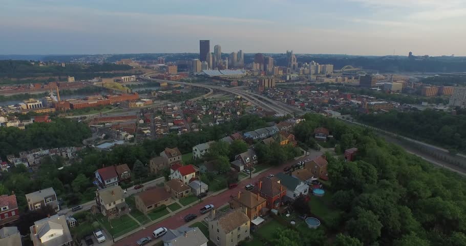 An aerial approach to Pittsburgh, Pennsylvania from the north.  The city is revealed by a neighborhood nestled in the trees on top of a hill.