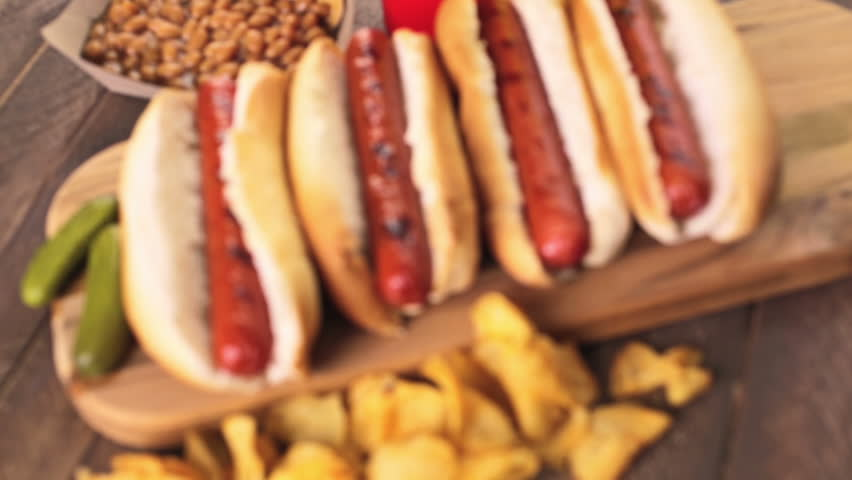 Grilled hot dogs on a white hot dog buns with chips and baked beans on the side.   Shutterstock HD Video #10961864