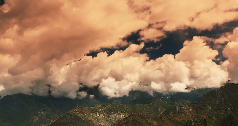 4k time lapse of white puffy clouds mass rolling over Tibet mountaintop,sunset glow,clouds shadow running,roof of the World. gh2_08756_4k