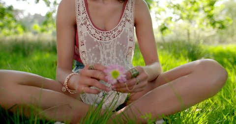 Smiling boho girl wearing vintage lace headband holding a pink daisy flower in a summer park, Panning in Slow Motion