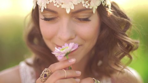 Daydreaming girl in boho fashion with a vintage lace headband smelling a flower while sitting in a sunlit summer park