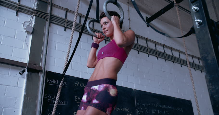 Fit girl looking focused and determined while doing pull-ups in a gym on gymnastic rings