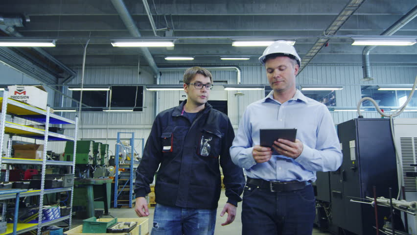 Engineer in Hard Hat and Factory Worker are Walking through Production Facility. Shot on RED Cinema Camera in 4K (UHD). | Shutterstock HD Video #11043851