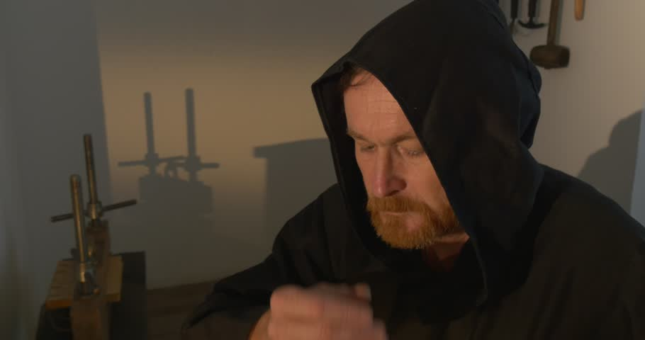 Monk, man with beard and mustache in Black Clothes, Black Hood, Leafing Through the Book