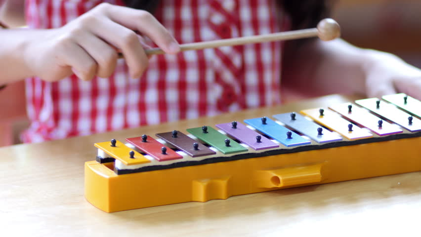 Asian Children playing on colorful xylophone, Pan shot