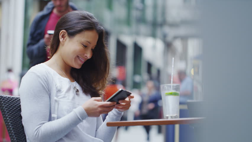4K Attractive young woman at an outdoor table using her smart phone in slow motion, shot on RED EPIC