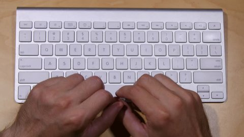 Typing on a wireless keyboard from an overhead perspective.