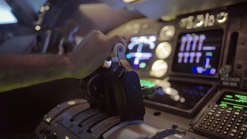 Detail shot of airline pilot pushing throttle forward and then pulling back in the cockpit of a jumbo jet.  Side view, hand-held camera, originally recorded in 4K.