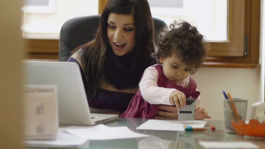 Multitasking mother, busy mom and businesswoman working with laptop computer at home and playing with her baby girl. Dolly shot   Shutterstock HD Video #1116373