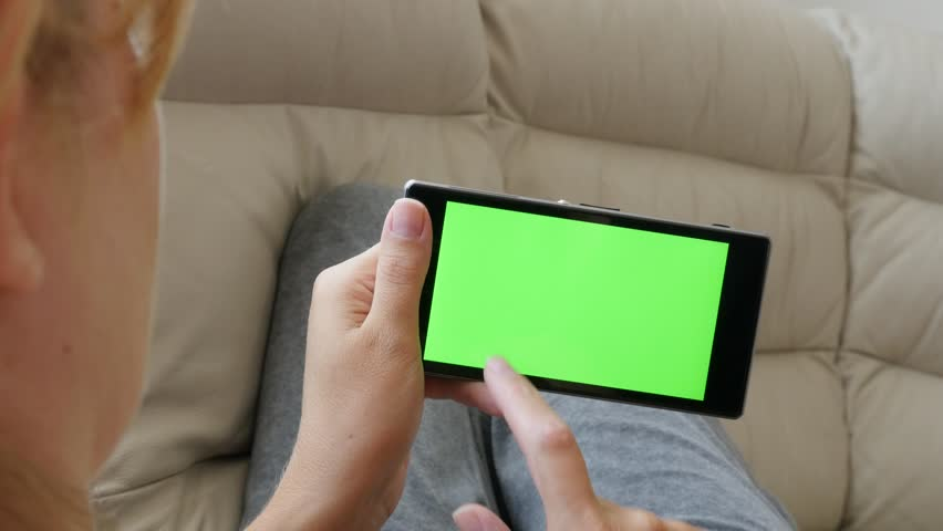 Woman relaxing and scrolling pages on greenscreen smart phone display 4K 2160p UltraHD footage - Female holding cell phone with touchscreen in hands 4K 3840X2160 30fps UHD video | Shutterstock HD Video #11166164