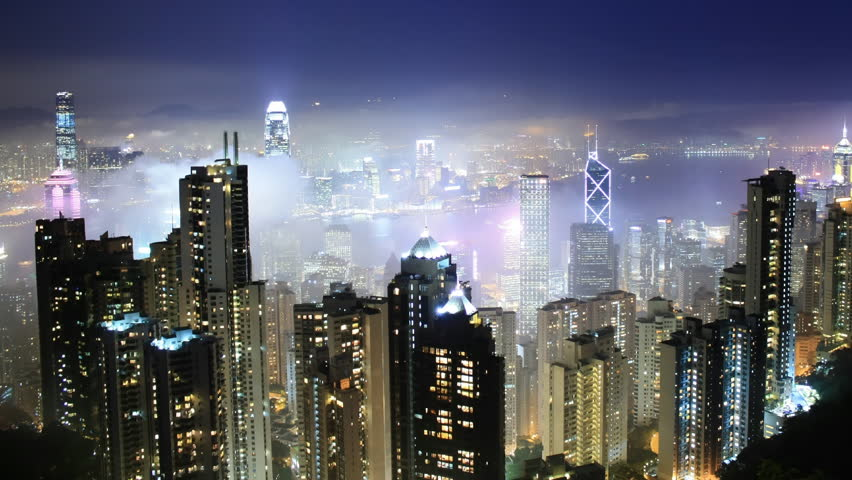 Time lapse Hong Kong skyline from famous Peak View at night. Fog comes into the city.