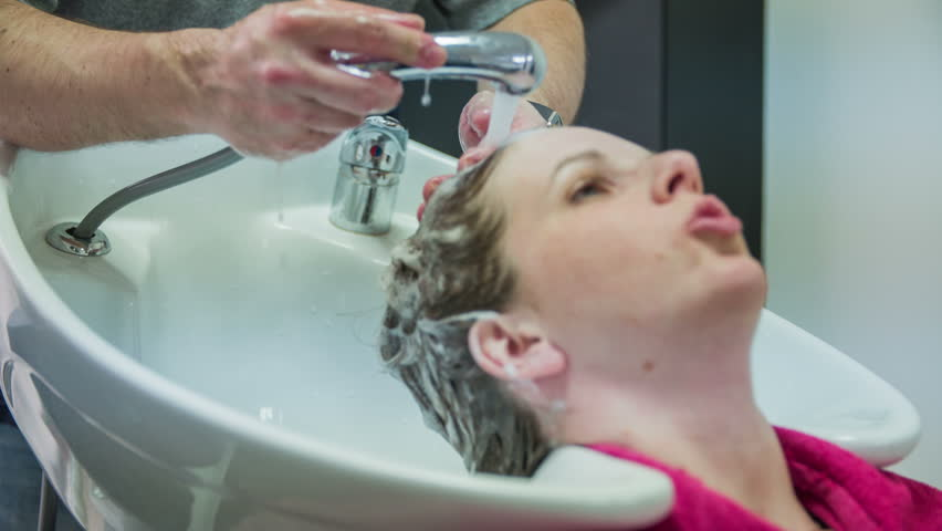 Male hairdresser preparing soap for washing hair 4k woman with hair washing of shampoo from woman hair close up 4k young female person visiting hairdresser salon winobraniefo Gallery