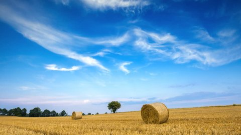 Stubble field with straw bales under blue sky with cirrus clouds. 4k timelapse 4096x2304