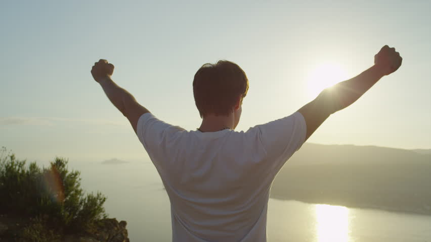 SLOW MOTION CLOSE UP: Successful young man with arms raised high standing on top of the ocean cliff above the city at beautiful golden sunset, sun shining through the hands #11223014
