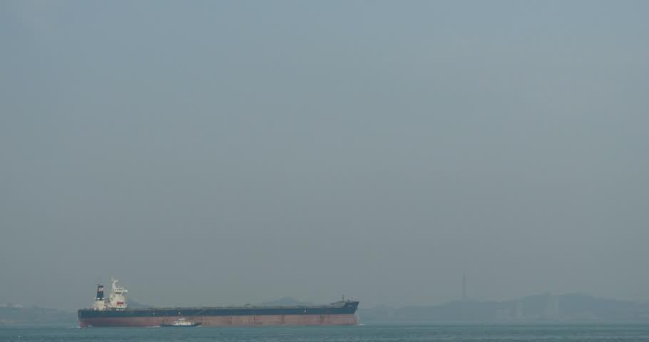 MAY 15,2015:4k timelapse Huge container oil tanker ship on ocean,modern building background. gh2_10952_4k
