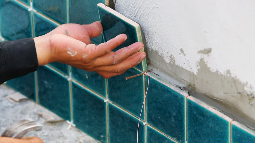 Putting Ceramic Tile On The Wall. Ceramist Is Slowly Laying Ceramic ...