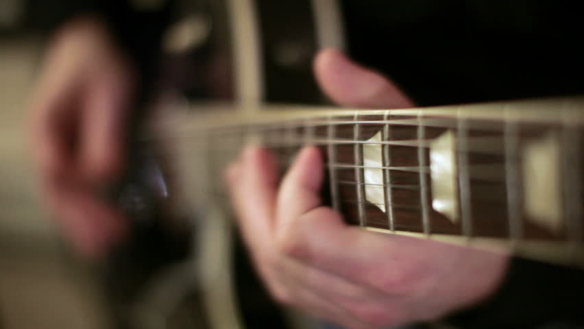 A shallow depth of filed look at a guitar is being played