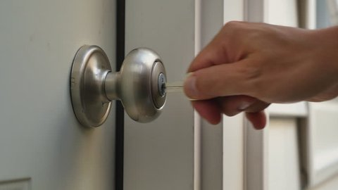 A man unlocks a house's door and enters.
