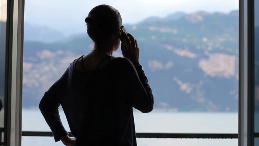 Silhouette of woman on the phone in front of the big window | Shutterstock HD Video #11309384