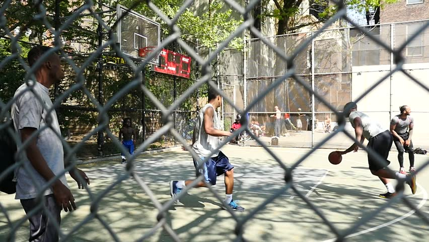 """NEW YORK CITY - CIRCA MAY 2015: (slow motion) West 4th Street's iconic basketball court, """"the cage"""" because a 20-foot chain-link fence boxes players, has been a proving ground for NBA stars."""