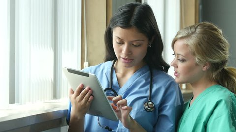 Two nurses consulting and looking at information on an ipad/tablet, close up shot