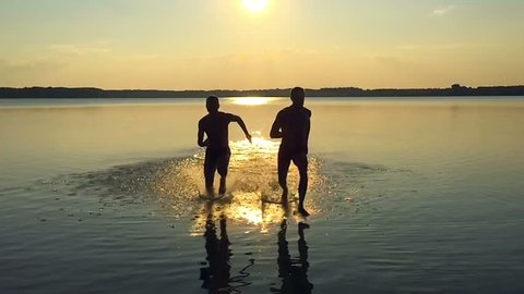 SLOW MOTION: Two men running along the water