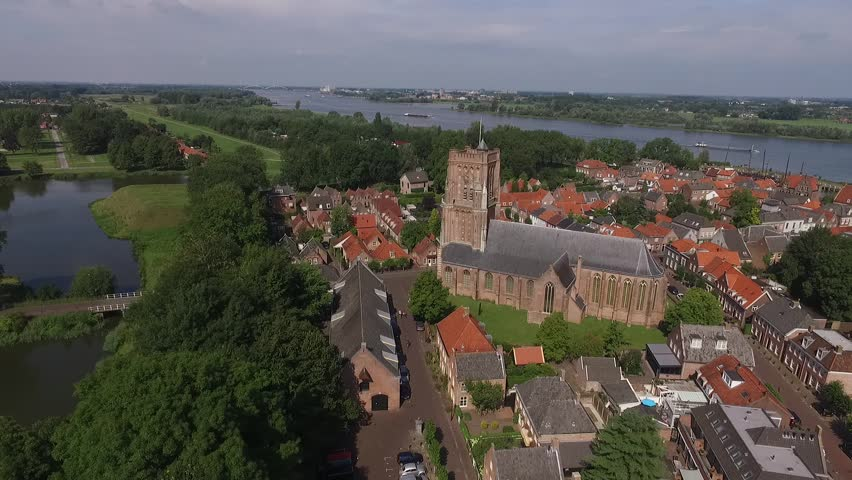Windmill And Church In The Historical Town Of Woudrichem In The