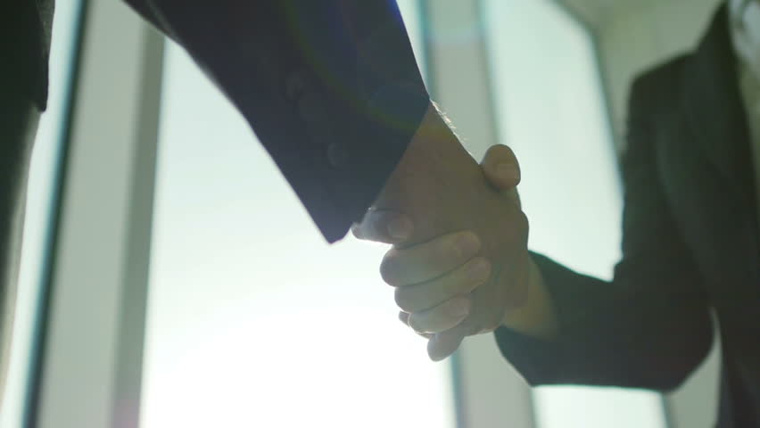 Two business partner shake hands when meeting. In...
