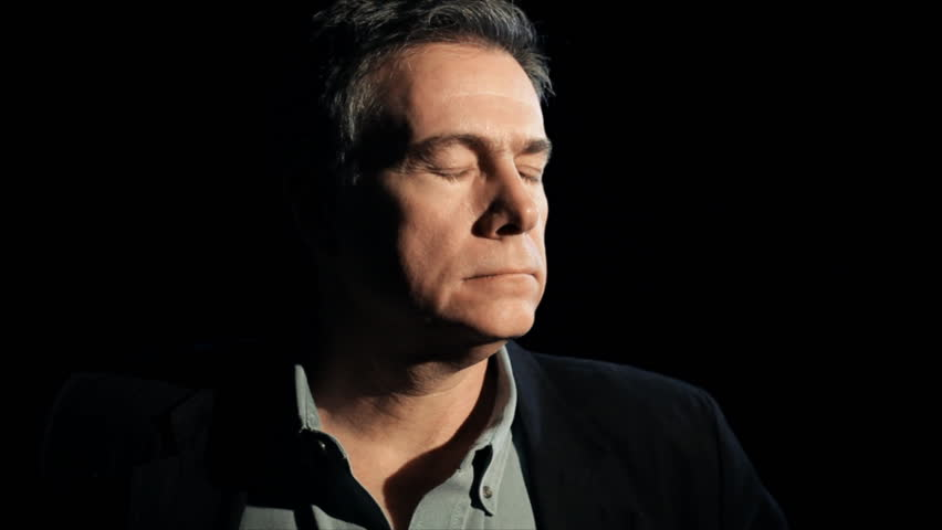 A dark backdrop and harsh lighting frames a mature melancholy man stopping and staring solemnly into the camera.