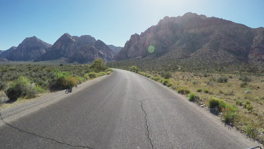 Viewpoint of a motorcyclist riding in Nevada Red Rock Canyon in 4K format. A biker rides down a scenic and empty road toward the mountains.