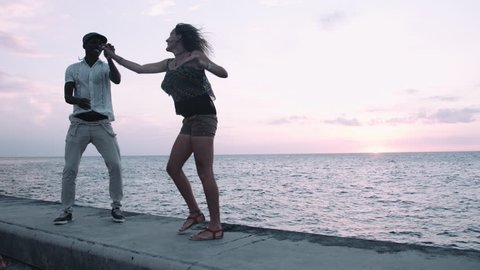 Young man and woman enjoying salsa dance on retaining wall at sunset, sea in background