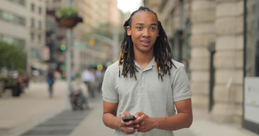 Young African American Black Asian mixed man walking and texting on city street | Shutterstock HD Video #11427524