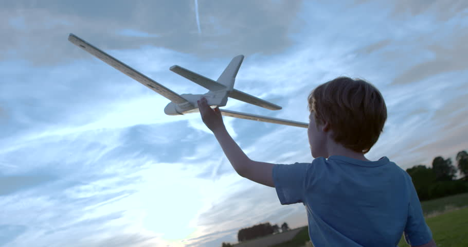 Boy playing outside with toy airplane  slow motion...