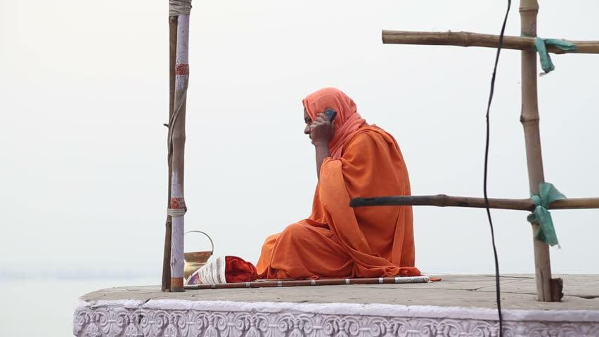 VARANASI, INDIA - 22 FEBRUARY 2015: Man in traditional clothing sitting at street in Varanasi and talking on phone.