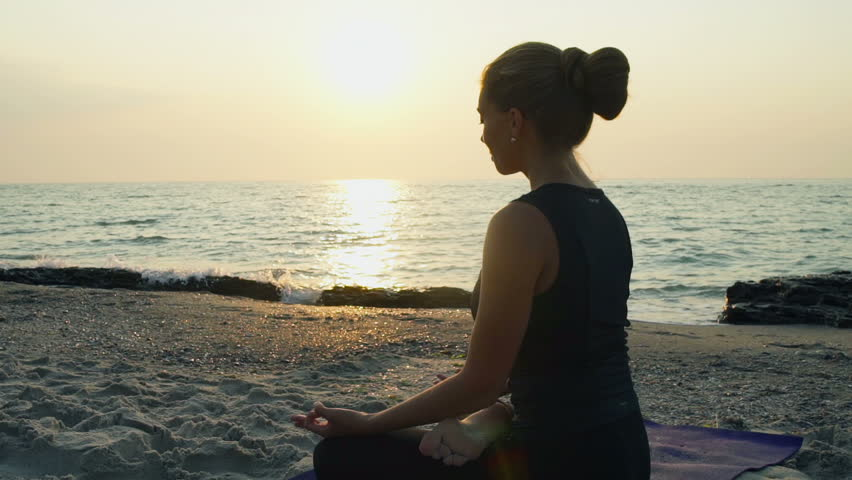 young female meditates on the beach slow motion #11479574