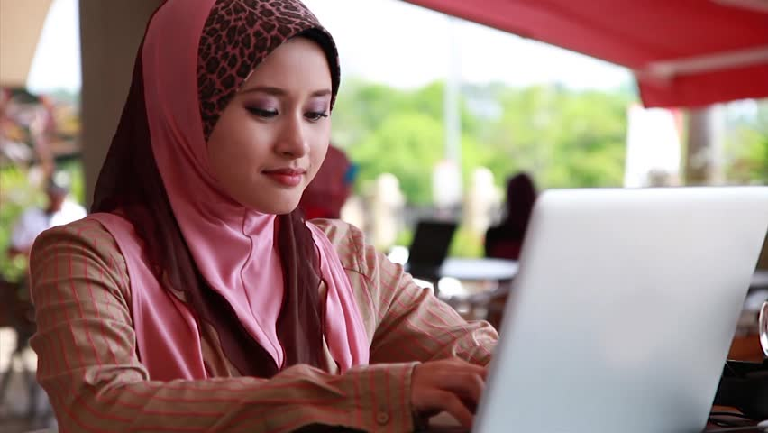 Young Muslim Girl using laptop and smiling at the camera