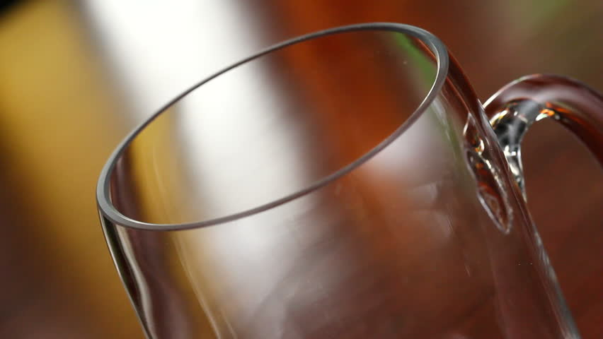 A bottle of beer is poured into a mug in a bar