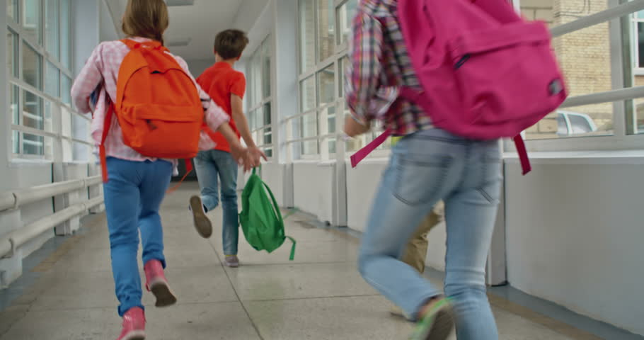 Schoolboy swinging his book bag and running down corridor, his friends following him