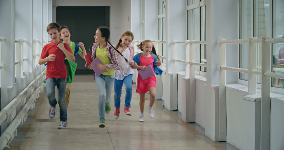 Excited pupils running down school corridor towards camera