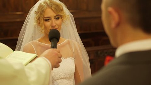 Bride taking wedding vows in church. Priest holding microphone for bride taking wedding vows. Beautiful female is looking at groom while taking oaths in church.