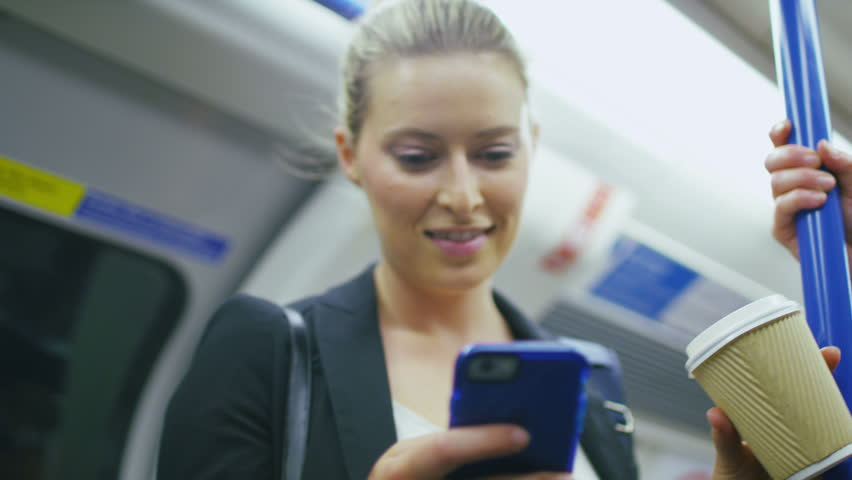 4K Attractive business woman standing on a train drinking from a coffee cup whilst reading her phone, shot on RED EPIC | Shutterstock HD Video #11557814